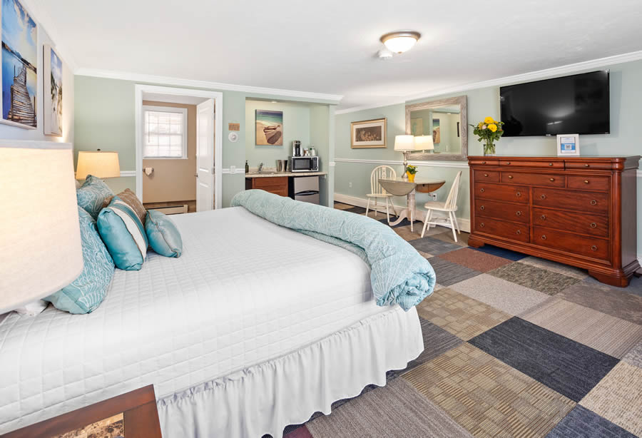 nantasket beach hotel king guest room with bed and dresser and kitchenette